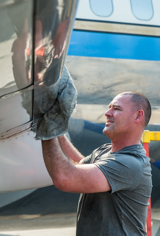 Staff Sgt. Bret Gratien, 436th Maintenance Squadron aircraft hydraulic section noncommissioned officer in charge, removes cleaning compound from the leading edge of the right wing on a McDonnell Douglas VC-9C Aug. 25, 2020, at Air Mobility Command Museum on Dover Air Force Base, Delaware. Gratien, along with other members of the hydraulic section, volunteered to strip, clean and polish the shiny aluminum skin of the aircraft formerly designated as Air Force Two. (U.S. Air Force photo by Roland Balik)