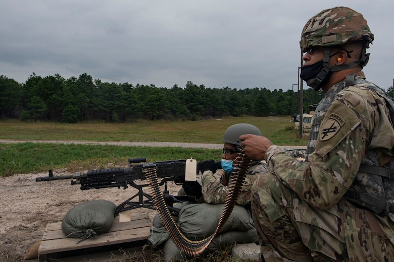Photo of a soldier holding ammunition for another soldier.