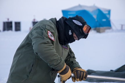 Captain Jason Grupp assists in building a polar chief arctic weather shelter as part of the ski way construction team during Air National Guard exercise Arctic Eagle  (U.S. Air National Guard photo by Technical Sergeant Jamie Spaulding/released)
