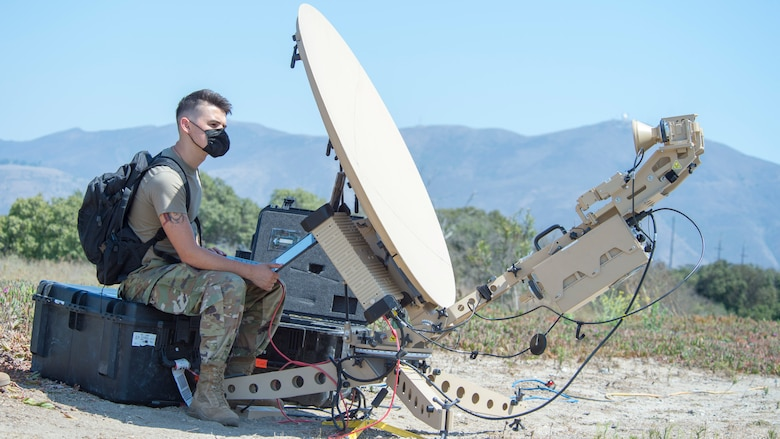 Senior Airman Peyton Van Nest, 51st Combat Communications Special Mission Squadron radio frequency transmission system technician from Robins Air Force Base, Georgia, sets up a satellite communications antenna during Exercise Agile Reaper, Sept. 5, 2020, at Naval Air Station Point Mugu, California. This routine exercise supports Total Force training and education of aircrew and support personnel to strengthen relationships, improve readiness, and boost lethality. (U.S. Air Force photo by Senior Airman Collette Brooks)