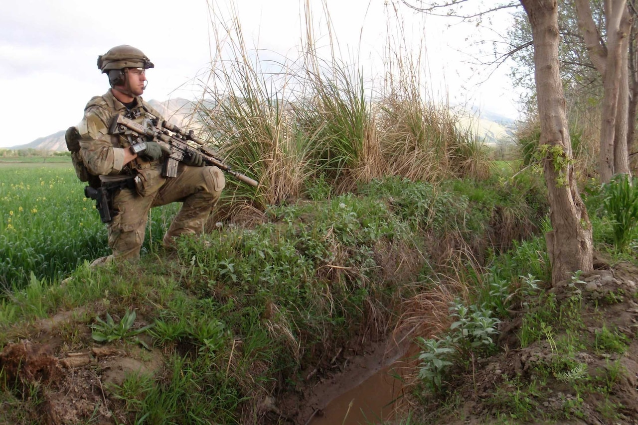 A soldier stands in a field while holding an automatic rifle.
