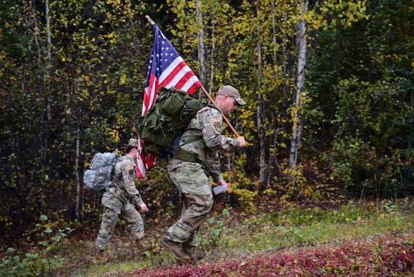 U.S. Air Force Tech. Sgt. Brandon Brown, the 354th Security Forces Squadron noncommissioned officer head of operations, carries an American flag during a 9/11 Remembrance Ruck on Eielson Air Force Base, Alaska, Sept. 11, 2020.