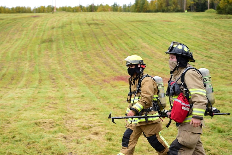 U.S. Air Force Airman 1st Class Logan Schaufelberger (left), a 354th Civil Engineering Squadron (CES) firefighter, and Senior Airman Alexander Kenneth Stewart, a 354th CES fire department vehicle operator, participate in a 9/11 Remembrance Ruck on Eielson Air Force Base, Alaska, Sept. 11, 2020.