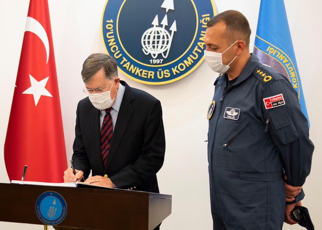 U.S. Ambassador to Turkey David Satterfield signs a guest book at the Turkish Command building while Turkish Air Force Col. Hakan Aki, 10th Tanker Wing chief of operations, watches.