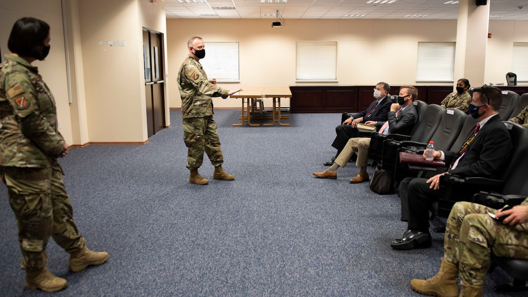 Incirlik Air Base commanders stand while talking about the base mission to visiting ambassador and his colleges in a conference room.