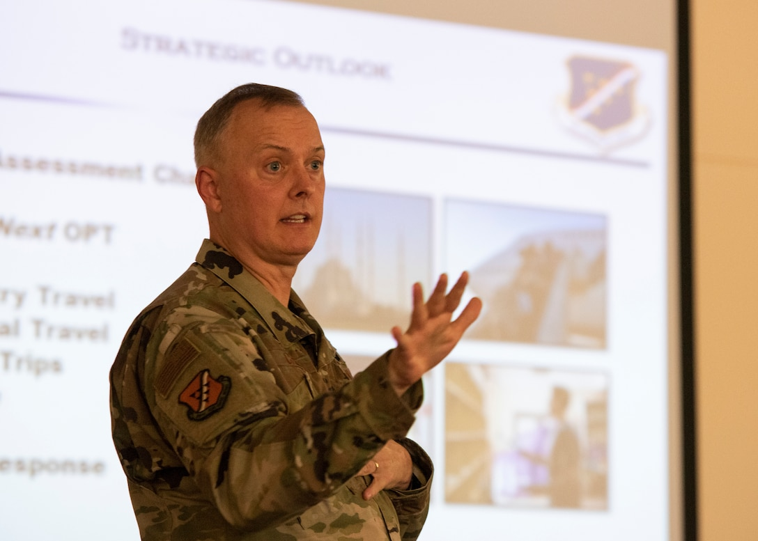 "Col. John Creel, 39th Air Base Wing commander, stands in front of a projector screen and talks with gestures to an audience about the projected slide. The slide says ""strategic outlook"" and contains pictures from various areas."