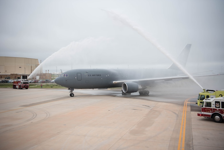 Gray airplane being sprayed by fire trucks