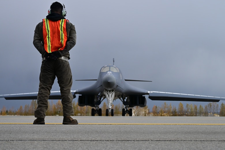 Photo of Airman marshaling a B-1