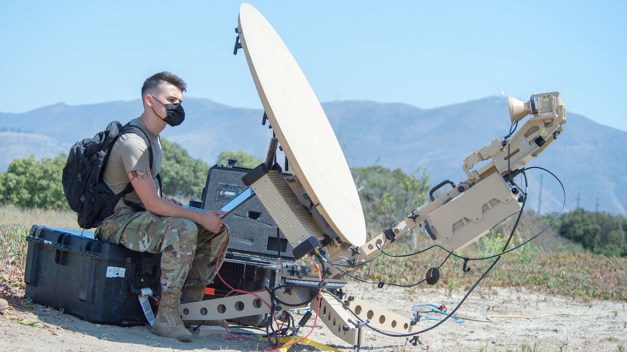 A man in a military uniform sits outside on a large box next to a satellite communications dish.