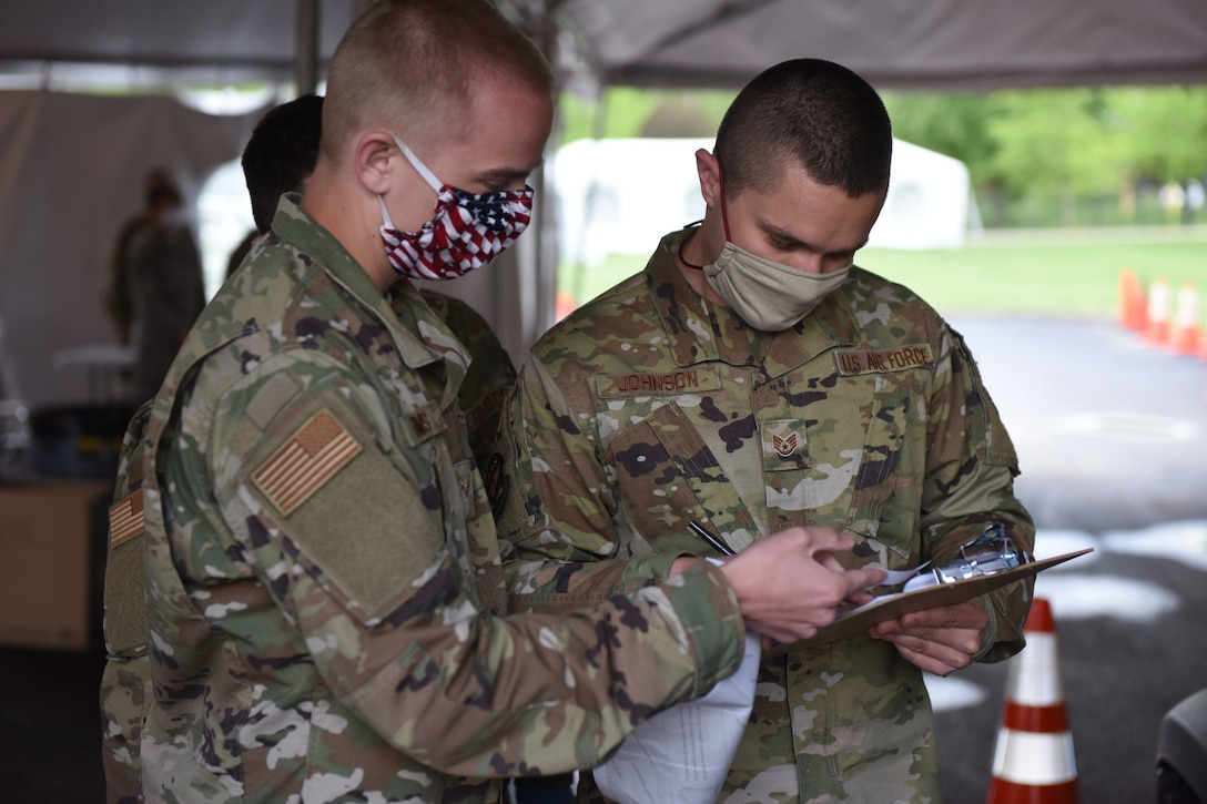 Two uniformed Illinois Air National Guard members check the serial number of a COVID-19 test kit for accuracy.