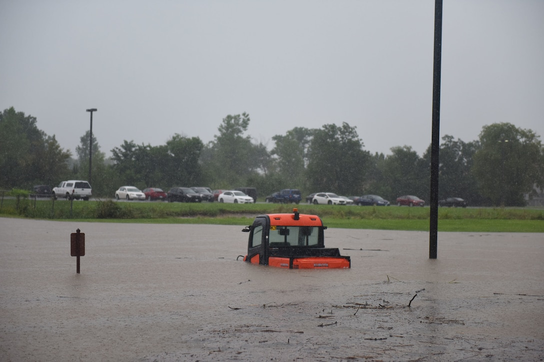 Photo of small utility vehicle in waist deep flood waters.
