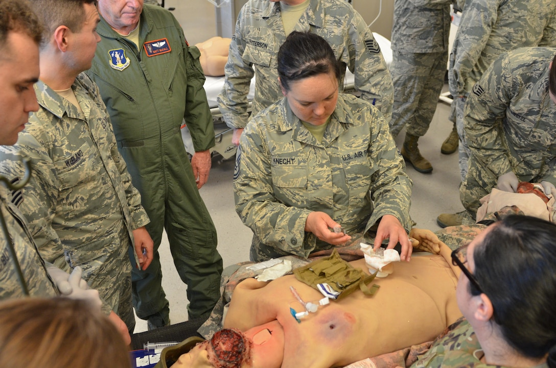 A uniformed team of Air National Guard medical technicians practice combat care on training dummies.