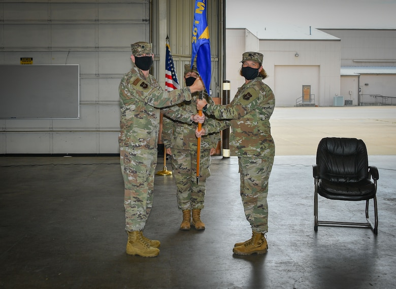 (Left to right) Lt. Col. Jeremy Moore, 301st Mission Support Group, deputy commander, hands the 301 FW LRS guidon to Lt. Col. Farrah Schluter during the 301st Fighter Wing Logistics Readiness Squadron Assumption of Command, September 13, 2020, at U.S. Naval Air Station Joint Reserve Base Fort Worth, Texas. The ceremony was limited to in-person personnel but also shared live on social media due to CDC protections. (U.S. Air Force photo by Staff Sgt. Randall Moose)