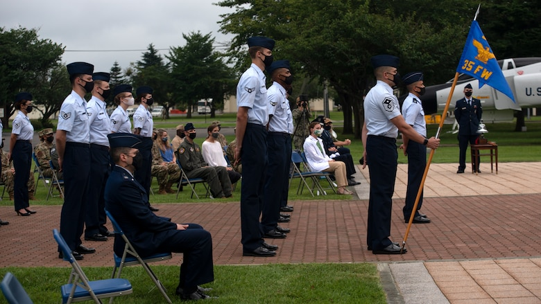 Individuals in uniform participate in an outdoor ceremony