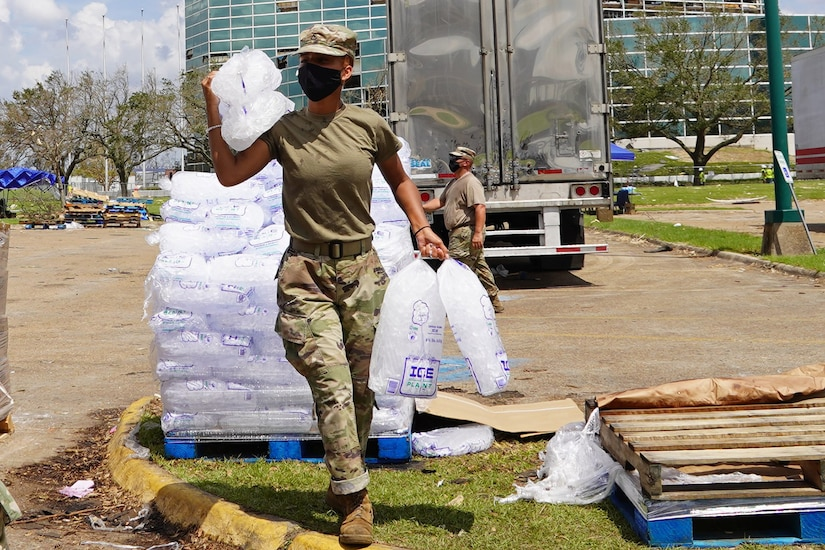 Louisiana National Guard Pfc. Reion Jones with the 1-141st Field Artillery Battalion, 256th Infantry Brigade Combat Team, hauls ice to a citizen's vehicle while working at a distribution site following Hurricane Laura in Lake Charles, Louisiana, Sept. 4, 2020.