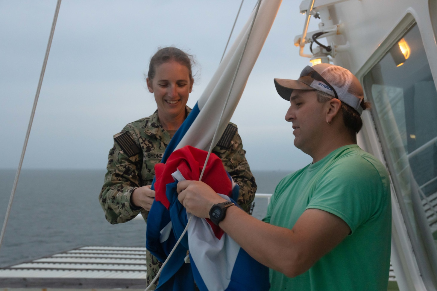 U.S. Navy Ens. Heather Bacon-Shone, Tactical Advisor (TACAD) with the Strategic Sealift Officer program, reviews tactical signaling with able-bodied seaman Joshua Sheldrick aboard the M/V Patriot during convoy operations in the Atlantic Ocean as part of DEFENDER-Europe 20.