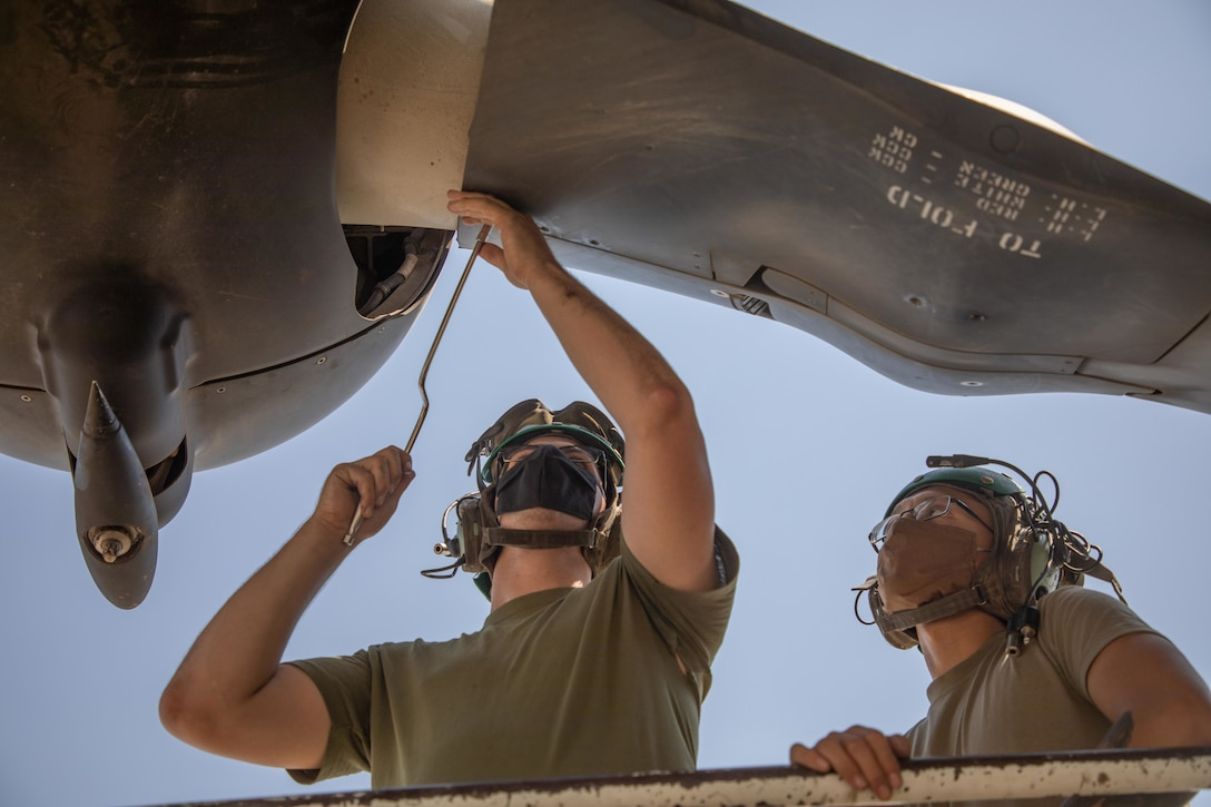 A U.S. Marine and a U.S. Navy Aviation Structural Mechanic Airman perform maintenance on a MV-22 Osprey in Kuwait, Aug. 5.