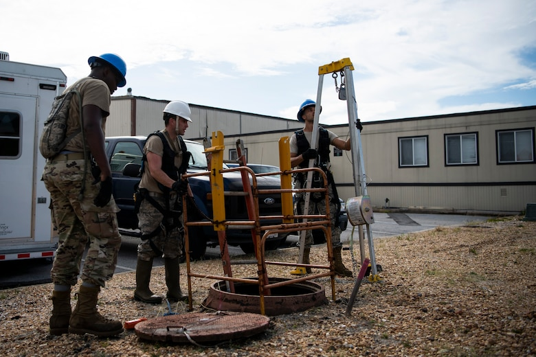 U.S. Air Force Senior Airman Darren Perry, left, Staff Sgt. Jesse Laclair, center, and Airman 1st Class Emmanuel Jackson-Wilson, right, cable antenna systems technicians with the 85th Engineering Installation Squadron assigned to Keesler Air Force Base, Mississippi, prepare to enter a manhole at Tyndall Air Force Base, Florida, Aug. 28, 2020. The 85th EIS has made multiple trips to Tyndall to assist the 325th Communications Squadron with relocating information transfer nodes. (U.S. Air Force photo by Tech. Sgt. Clayton Lenhardt)