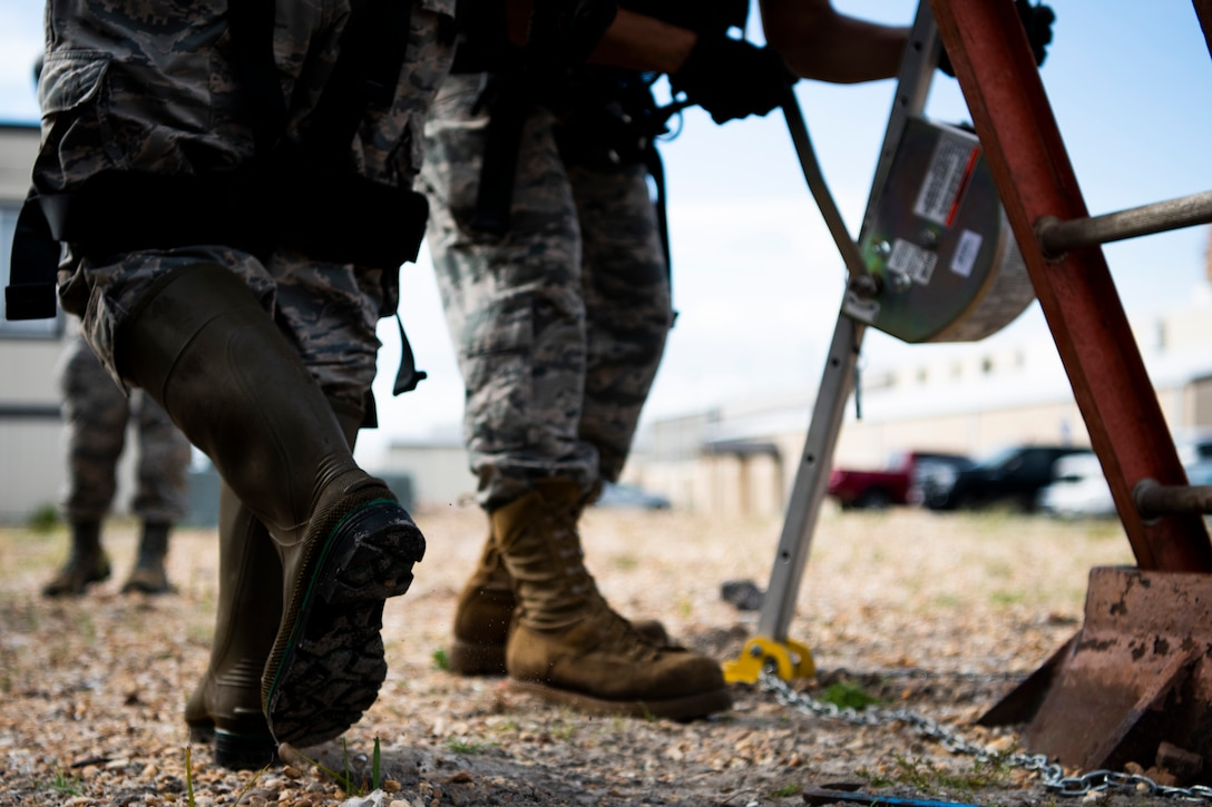Cable antenna systems technicians with the 85th Engineering Installation Squadron assigned to Keesler Air Force Base, Mississippi, prepare to enter a manhole at Tyndall Air Force Base, Florida, Aug. 28, 2020. The 85th EIS is assisting the 325th Communications Squadron to move information transfer nodes from damaged buildings, which will improve network stability. (U.S. Air Force photo by Tech. Sgt. Clayton Lenhardt)