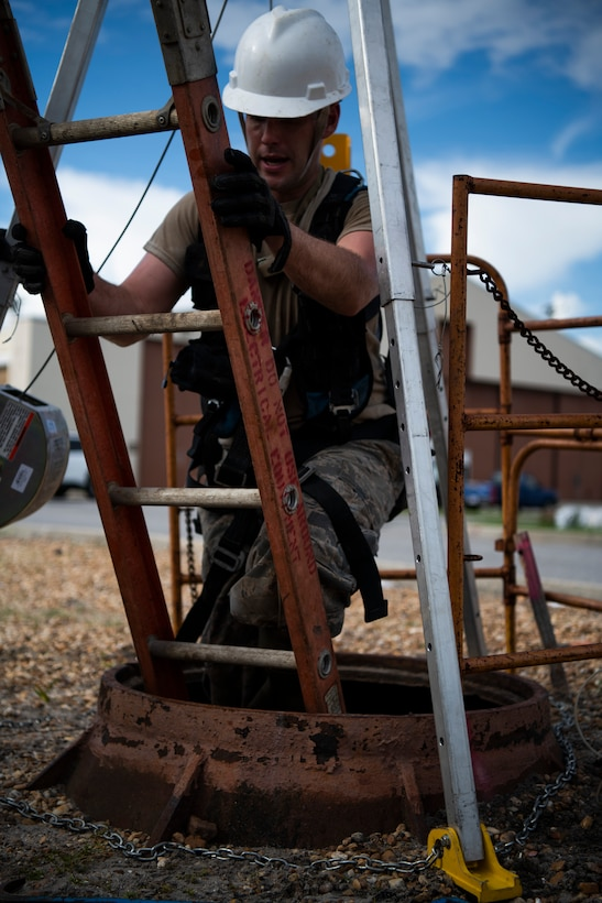 U.S. Air Force Staff Sgt. Jesse Laclair, cable antenna systems technician with the 85th Engineering Installation Squadron assigned to Keesler Air Force Base, Mississippi, enters a manhole to manage cable at Tyndall Air Force Base, Florida, Aug. 28, 2020. The 85th EIS has made multiple trips to Tyndall to assist the 325th Communications Squadron with relocating information transfer nodes. (U.S. Air Force photo by Tech. Sgt. Clayton Lenhardt)