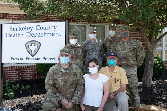 A local COVID-19 case investigation team stands outside of their work station at the Berkeley County Health Department, Martinsburg, W. Va., July 22, 2020. From left to right, front row, Tech. Sgt. Travis Sites, Elizabeth Aleong, Dr. Charles Devine, back row from left to right, 1st Lt. Jaymie Brooks Dumproff, SSgt Richard Calo, Airman 1st Class Andrew Shilling, and 2nd Lt. Ben Smith. Airmen and civilian volunteers have teamed up to administer contact tracing for the local community. Data gathered from positive and negative tests, phone calls and text messaging are entered into a database where COVID-19 patients and their contacts are tracked.