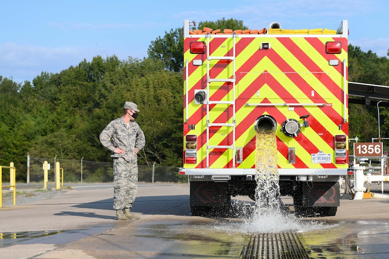 An Airman dumps water from a fire truck to simulate a fuel spill