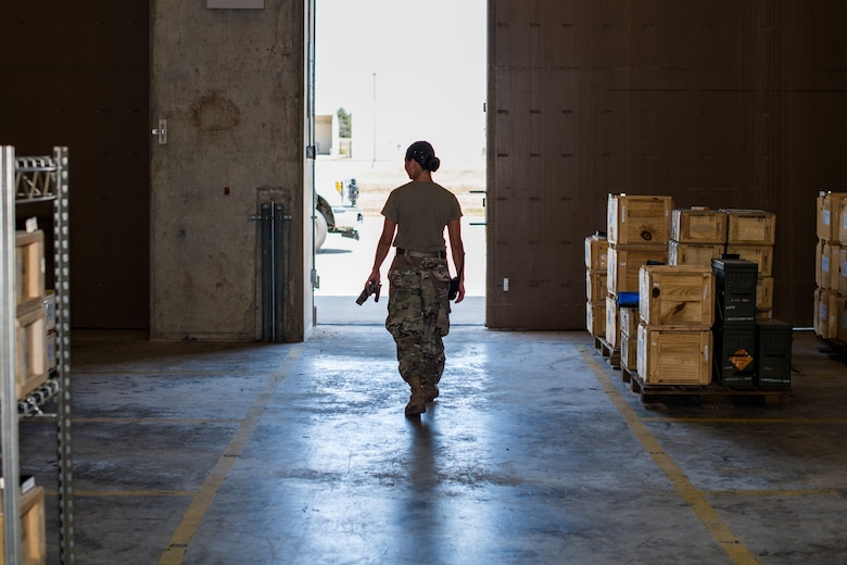 Senior Airman Marian Bock, 22nd Maintenance Squadron munitions flight custody accounts technician, exits an earth-covered magazine facility, or igloo, after performing inventory inspections Aug. 28, 2020, at McConnell Air Force Base, Kansas. Certain types of ammunition have to be stored in these earth covered facilities to meet safety regulations. (U.S. Air Force photo by Senior Airman Skyler Combs)