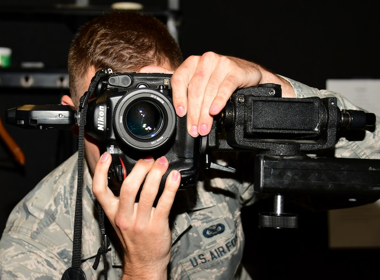 A photo of an airman taking a photo in the studio.