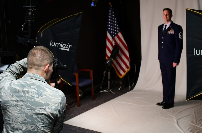 A photo of an airman taking a photo of another airman in the studio.