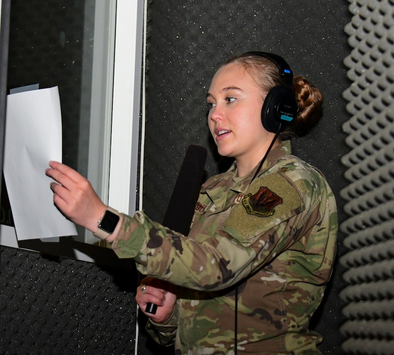 A photo of an airman sitting in a sound booth to voice a script.