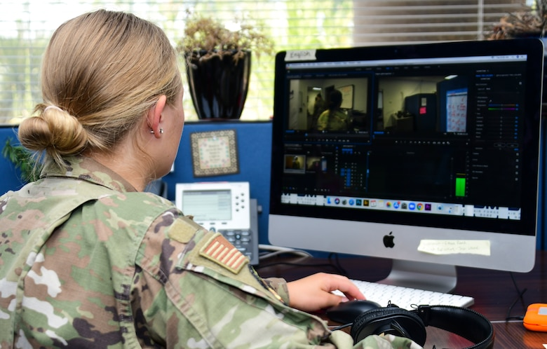 A photo of an airman editing her video footage in Adobe premiere.