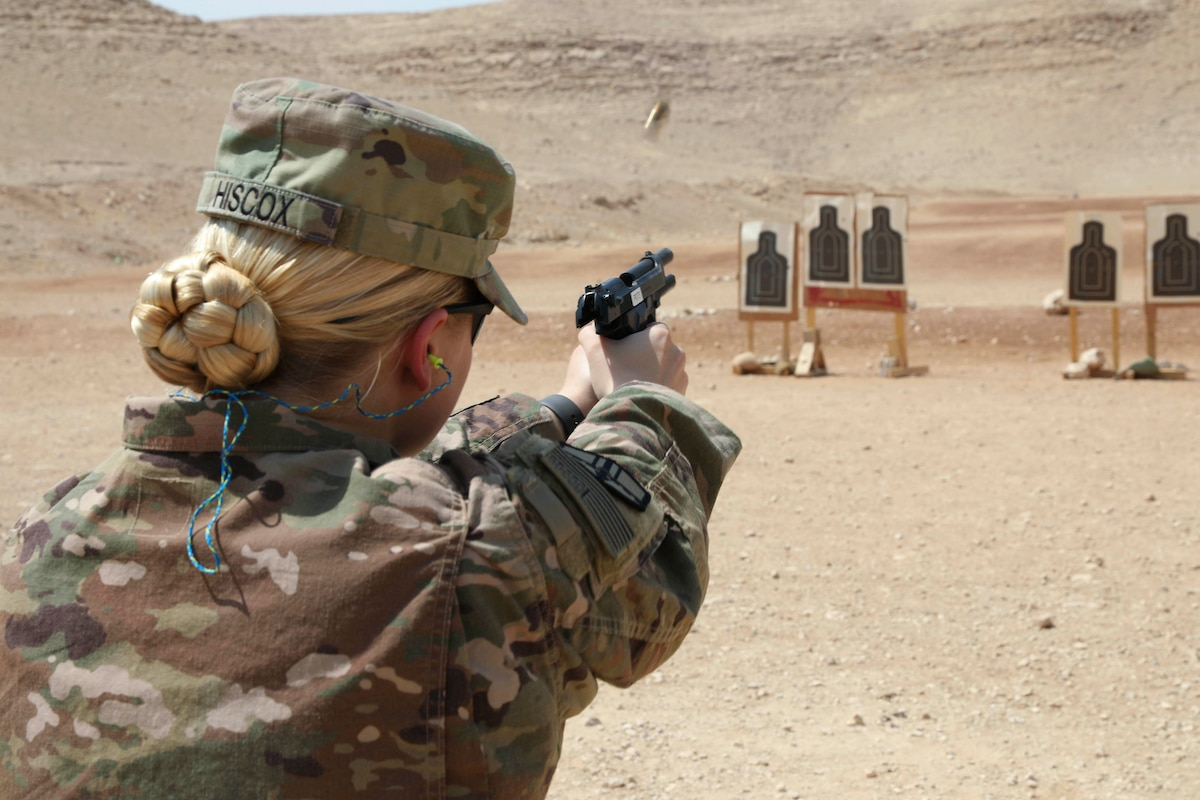 A soldier fires a weapon at a training target in a desert-like area.