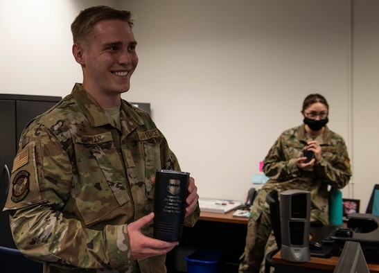 U.S. Air Force Airman 1st Class Parker Pfeffer, 20th Comptroller Squadron (CPTS) financial operations technician, smiles holding Weasel of the Week mug with his supervisor, Staff Sgt.Toniya Murar, 20th CPTS financial operations supervisor, also smiling.