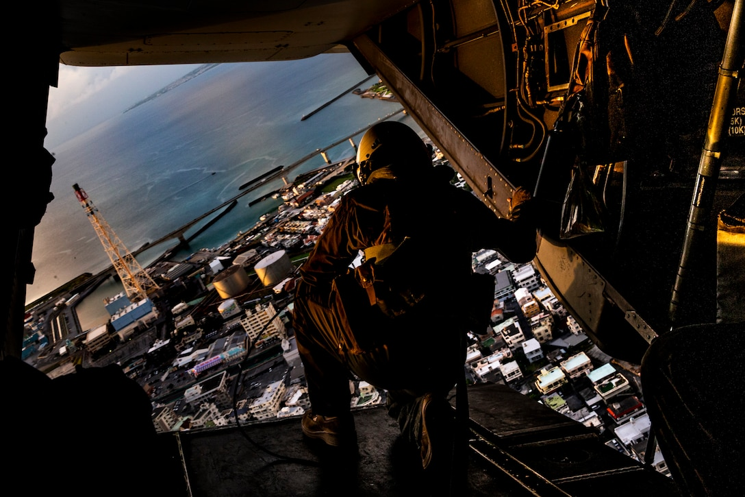 A U.S. Marine flies over Okinawa while aboard an MV-22 Osprey during Operation Lightning Strike, Aug. 6.