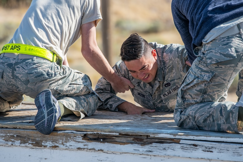 U.S. Air Force Senior Airman Hollan Moore, a reservist in the 419th Fighter Wing, pulls himself up with the help of fellow Airmen during an obstacle course