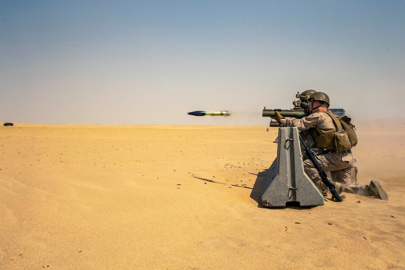 Marines fire a weapon in a desert-like area.