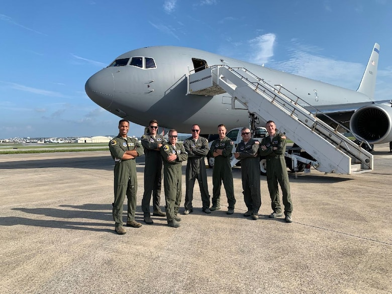 From left, Capt. Erik Earle, Capt. Chris Schimmel, Maj. Matt Valentino, Master Sgt. Brett Peterson, Capt. Jordan Gauvin, Chief Master Sgt. Michael George and Maj. Leon Rice pose in front of a KC-46A Pegasus, Sept. 8, 2020, at Kadena Air Base, Japan. The Pease airmen executed the first official transoceanic coronet ever accomplished with a Pegaus refueler, which began Sept. 9 and involved 16 aerial refuelings of five F/A-18 jets. (courtesy photo)