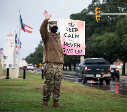 """Master Sgt. Tiffany Arrington, 12th Operations Group first sergeant, waves at people driving past her during the """"We Care"""" event at Joint Base San Antonio-Randolph Sept. 10."""