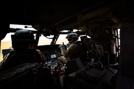 Two Black Hawk helicopter pilots speak to one another in the cockpit of their helicopter during water drop training in California.