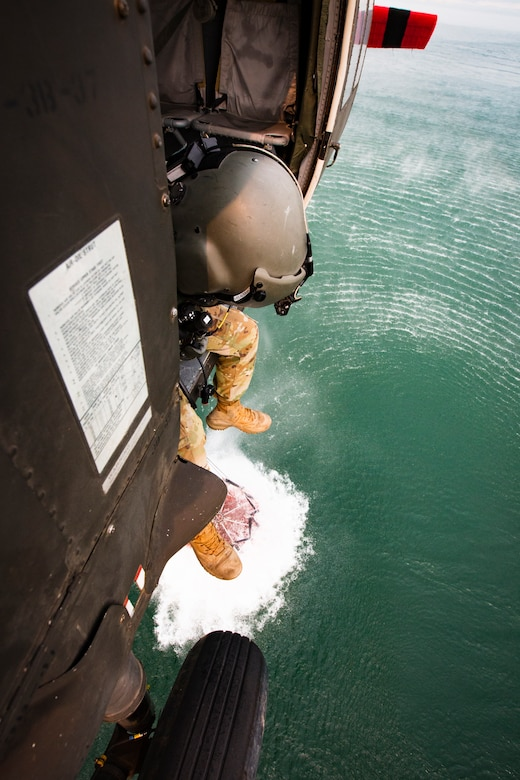 A solder looks out the side of a Black Hawk helicopter during water drop training, while they hover over Folsom Lake.