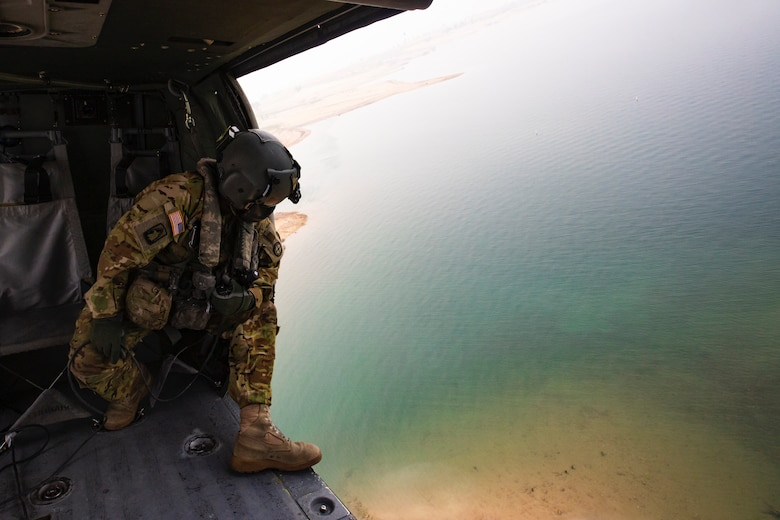 A soldier looks out from a Black Hawk helicopter during water drop training as they hover over Folsom Lake.