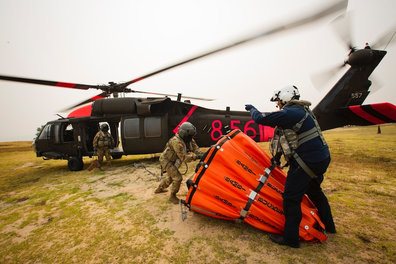 Two men, one military and one a civilian, load a water bucket onto a helicopter.
