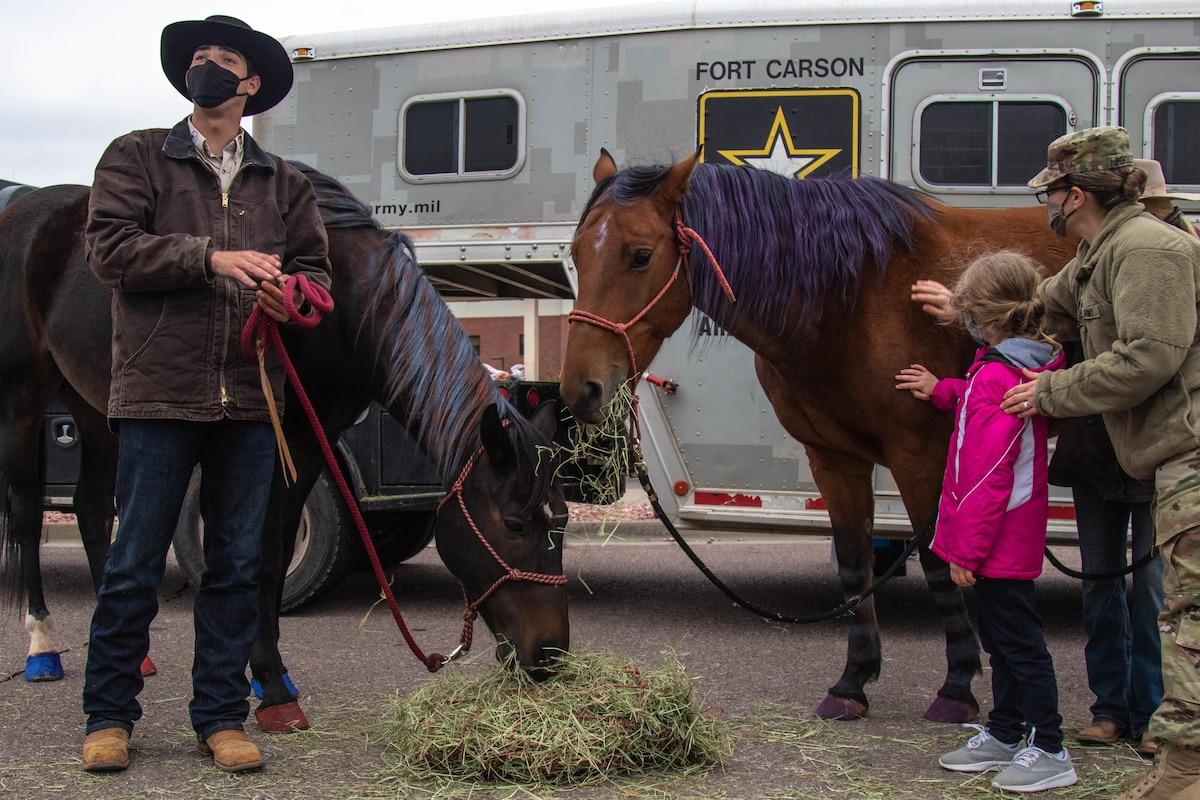 A woman and a child pet a horse while a man with a cowboy hat stands at one side.