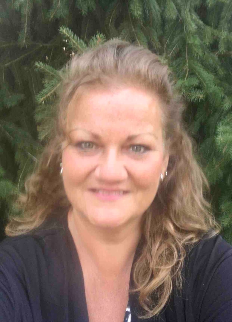 Tracy Hart headshot with a tree in background.