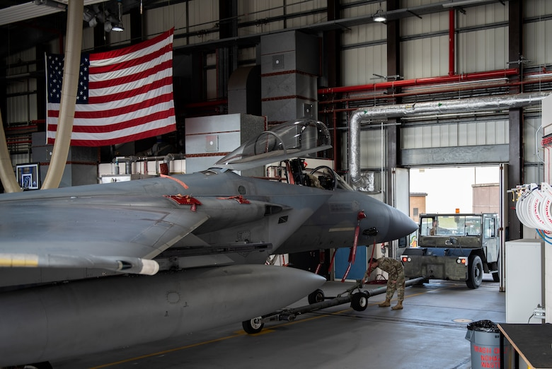 U.S. Air Force Airmen, assigned to the 48th Component Maintenance Squadron fuels shop, tow an F-15C Eagle into the hangar during an Agile Combat Employment training at Royal Air Force Lakenheath, England, Aug. 31, 2020. The training was designed to enhance ACE  capabilities by teaching Airmen to perform multiple roles outside the scope of their regular daily duties. (U.S. Air Force photo by Airman 1st Class Jessi Monte)