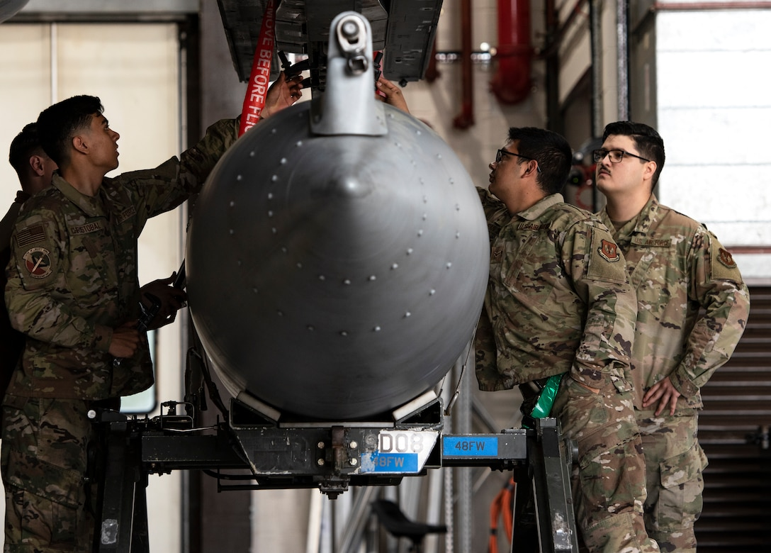 U.S. Air Force Airmen, assigned to the 48th Component Maintenance Squadron fuels systems maintenance shop, learn how to attach an external fuel tank to an F-15C Eagle during an Agile Combat Employment training at Royal Air Force Lakenheath, England, Aug. 31, 2020. Proficiency in a multitude of skills allows Airmen to more effectively and efficiently respond to unique scenarios and potential threats, which is a key aspect of the ACE initiative. (U.S. Air Force photo by Airman 1st Class Jessi Monte)