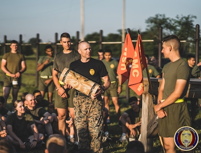 MSgt Hatfield, the Course Chief of the Military Police Basic Course, presents a memento to the class who won a physical fitness competition while competing against all other classes from the Marine Corps' Military Police School.