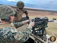 Sgt White observes impacts on target as he coaches a Military student on the proper employment of the MK-19 grenade launcher.