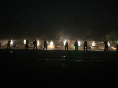 Students of the Military Police Basic Course conduct live-fire training in a low-light environment.