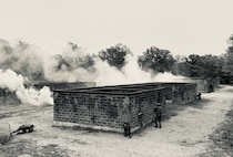 Students conduct a raid on an urban village during the culminating Field Training Exercise of the Military Police Basic Course. Smoke is deployed tactically to obscure the movement of Marines as they maneuver through their objective.